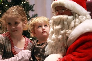 """Hope Nowell, 2, center, stares up at Santa Claus while she and her sister Macy Nowell, 10, get their picture made Saturday morning during the 13th annual Breakfast with Santa entitled """"A Magical Breakfast with Santa"""" at the Vicksburg Convention Center. More than 600 people attended the annual event which was sponsored by Walmart and McDonald's, with part of the proceeds raised going to the Ronald McDonald House. (Justin Sellers/The Vicksburg Post)"""
