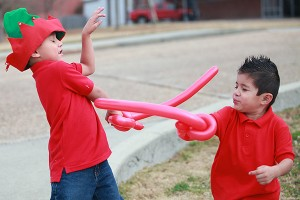 """Brothers Eric, 6, and Christian Reyna, 4, sword fight with balloon swords made by magician Dorian LaChance Saturday morning during the 13th annual Breakfast with Santa entitled """"A Magical Breakfast with Santa"""" at the Vicksburg Convention Center. More than 600 people attended the annual event which was sponsored by Walmart and McDonald's, with part of the proceeds raised going to the Ronald McDonald House. (Justin Sellers/The Vicksburg Post)"""