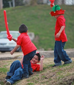 """Ivan Reyna, 7, lays on the ground while being play-attacked by his brothers Christian, 4, left, and Eric, 6, with balloon swords made by magician Dorian LaChance Saturday morning during the 13th annual Breakfast with Santa entitled """"A Magical Breakfast with Santa"""" at the Vicksburg Convention Center. More than 600 people attended the annual event which was sponsored by Walmart and McDonald's, with part of the proceeds raised going to the Ronald McDonald House. (Justin Sellers/The Vicksburg Post)"""