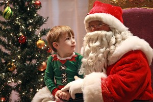 """Tylan Ainsworth, 2, looks at Santa Claus while having their picture made Saturday morning during the 13th annual Breakfast with Santa entitled """"A Magical Breakfast with Santa"""" at the Vicksburg Convention Center. More than 600 people attended the annual event which was sponsored by Walmart and McDonald's, with part of the proceeds raised going to the Ronald McDonald House. (Justin Sellers/The Vicksburg Post)"""