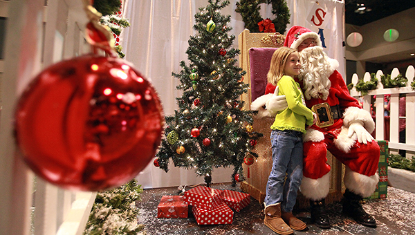 Anna Walker, 6, has her picture made with Santa Claus. (Justin Sellers/The Vicksburg Post)
