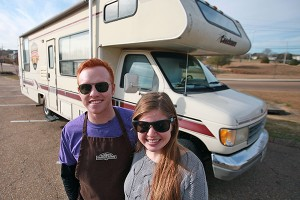 """Documentary makers Alyssa and Heath Padgett stand in front of their RV in the parking lot of the Outlets at Vicksburg after filming Wednesday at Rocky Mountain Chocolate Factory. The couple is filming a cross country documentary titled """"Hourly America"""" in which they work hourly-wage jobs in all 50 states. (Justin Sellers/The Vicksburg Post)"""