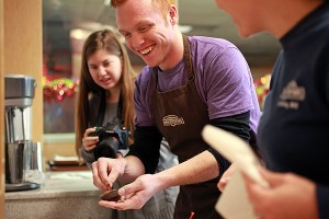 """Heath Padgett laughs while making chocolate-covered strawberries Wednesday at Rocky Mountain Chocolate Factory. Padgett and his wife Alyssa are filming a cross country documentary titled """"Hourly America"""" in which they work hourly-wage jobs in all 50 states. (Justin Sellers/The Vicksburg Post)"""