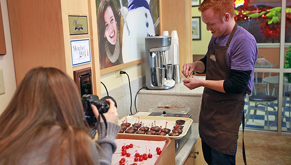 """Alyssa Padgett films her husband Heath make chocolate-covered strawberries Wednesday at Rocky Mountain Chocolate Factory. The couple is filming a cross country documentary titled """"Hourly America"""" in which they work hourly-wage jobs in all 50 states. (Justin Sellers/The Vicksburg Post)"""