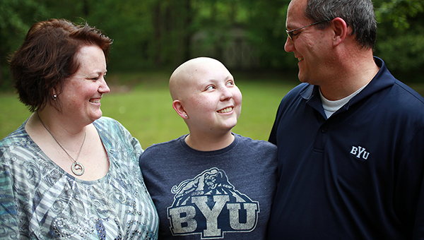 ALL TOGETHER: Afton Wallace, center, stands with her parents Rob and Sheri Friday outside their home. Afton, who was diagnosed with Ewings Sarcoma on May 22, 2014, has been accepted to Brigham Young University for the Fall 2015 semester. (Justin Sellers/The Vicksburg Post)