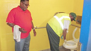Community service supervisor James Johnson, left, gives Mayor George Flaggs Jr. direction as the mayor cleans a toilet in one of the restrooms at Catfish Row.
